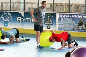 Hlavný tréner Andrej Kmeč dozerá na správne cviky počas strečingu.