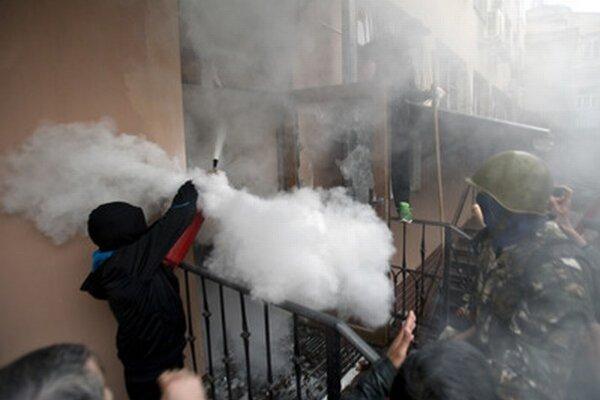 Demonštrant počas nedelných nepokojov s hasiacim prístrojom.