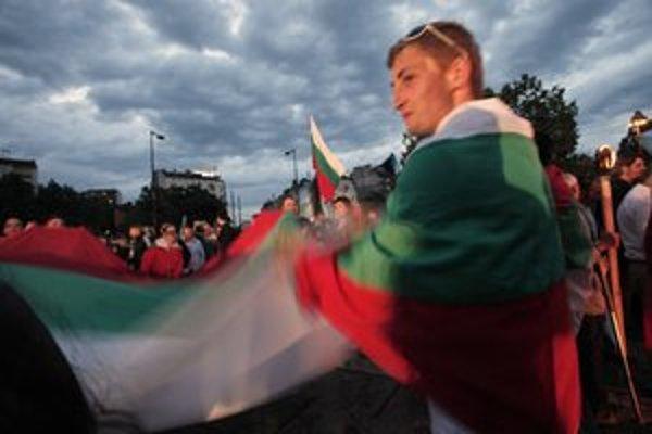 Protestujúci mávajú bulharskými vlajkami.