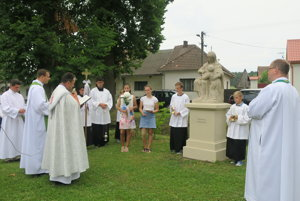 Socha predstavuje sediacu ženu - sv. Annu, ktorá z otvorenej knihy učí malé dievča - Pannu Máriu.