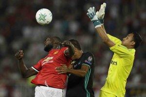 Útočník Manchestru United Romelu Lukaku (v červenom drese) v súboji s dvojicou Realu Madrid - obrancom Raphaelom Varanom (uprostred) a brankárom Keylorom Navasom.