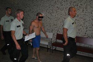Trojčlenná policajná eskorta privádza obvineného na Okresný súd Košice - okolie.