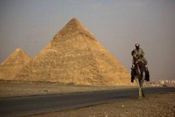 Egypťan na ťave čaká na turistov pred komplexom pyramíd v Gíze.