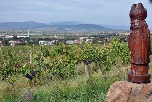 Pohľad na obec Čerhov, vpravo drevená socha sv.Urbana vo vinohradoch nad obcou.