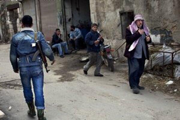Sýrčania kráčajú okolo vojaka Slobodnej sýrskej armády v severosýrskom meste Idlib.