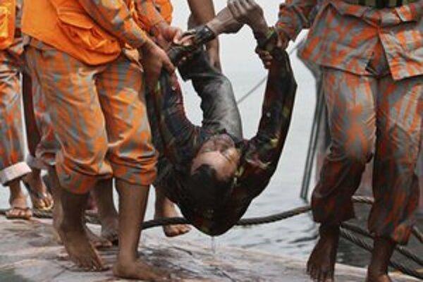 Záchranári s telom jednej z obetí.
