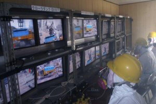 Pracovníci v ochranných odevoch sledujú radiáciu v tsunami poškodenej jadrovej elektrárni Fukušima.