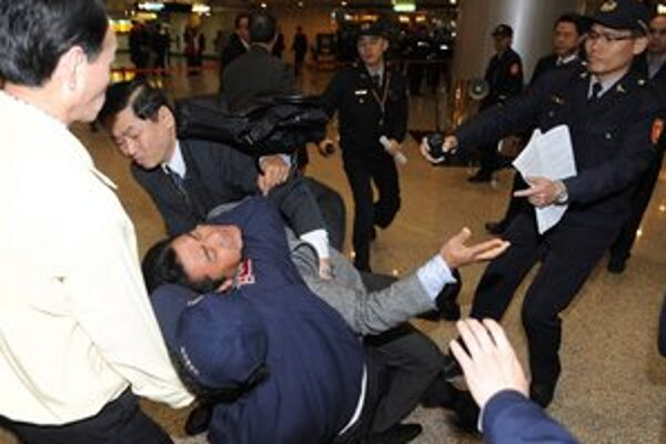 Pracovníci čínskej bezpečnostnej služby sa snažia spacifikovať tibetského aktivistu.