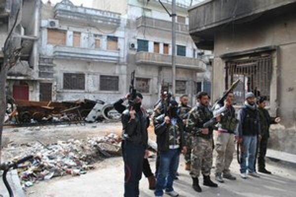 Rebeli pózujú v zničenej časti mesta Homs.