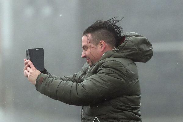 Muž si fotí selfie v silnom vetre v meste Lahinch na západnom pobeží Írska.