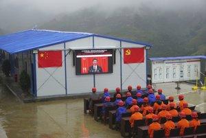 Robotníci sledujú na televíznej obrazovke prejav čínskeho prezidenta  Si Ťin-pchinga počas otvorenia 19. zjazdu Komunistickej strany Číny.
