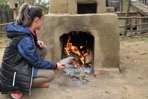 Na snímke dievča prikladá drevo do hlinenej pece.