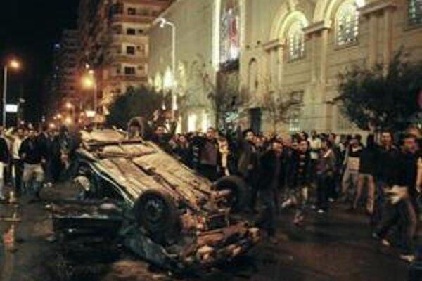 Ľudia vykrikujú pred vybuchnutým autom 1. januára 2011 v Alexandrii.