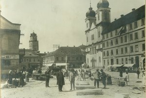 Masarykovo námestie v Trenčíne počas úpravy ciest v rokoch 1927 – 1929. Okrem spomínaných osôb (starostu a pracovníkov mestského úradu zodpovedných za úpravy) sa na fotke nachádza aj skupina ľudí, ktorí sa venujú svojím každodenným činnostiam – predaju tovaru alebo starostlivosti o výklady.
