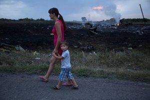 Miesta žena s dieťaťom prechádza okolo miesta dopadu lietadla.