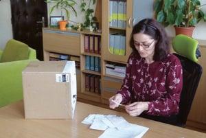 Riaditeľka číta lístočky zo schránky sťažností.