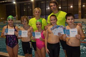 Ocenení plavci s trénermi Katkou Tomalovou a Jozefom Jedinákom.