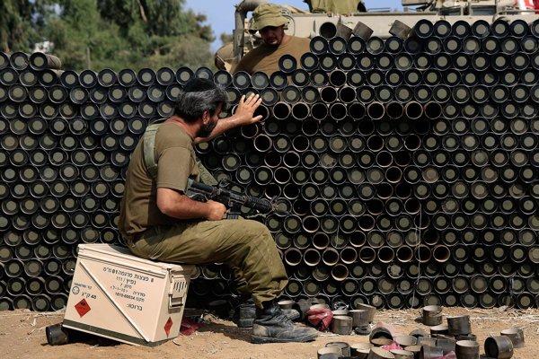 Izraelský vojak robí Dávidovu hviezdu z kartónových zvyškov munície pre mínomety. (AP Photo/Tsafrir Abayov)