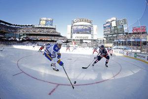 Jack Eichel z Buffala a obranca Rangers Ryan McDonagh bojujú o puk v priebehu zápasu NHL Winter Classic v New Yorku na štadióne CitiField.