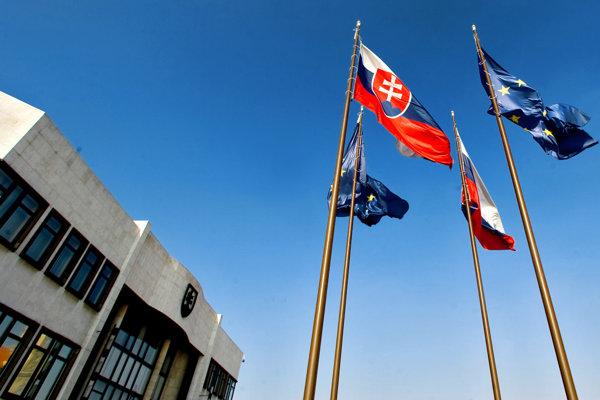 Vlajky Slovenska a Európskej únie pred budovou parlamentu.