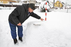 Ladislav Murín pri meraní výšky snehu. Časy, keď vOravskej Lesnej nebolo pre sneh vidno ploty, sú preč.