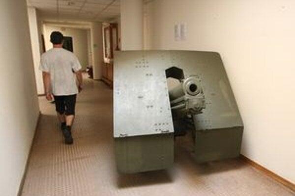 Poľný a protitankový kanón skladujú v kancelárskej časti budovy. Mnoho techniky chátra vonku.