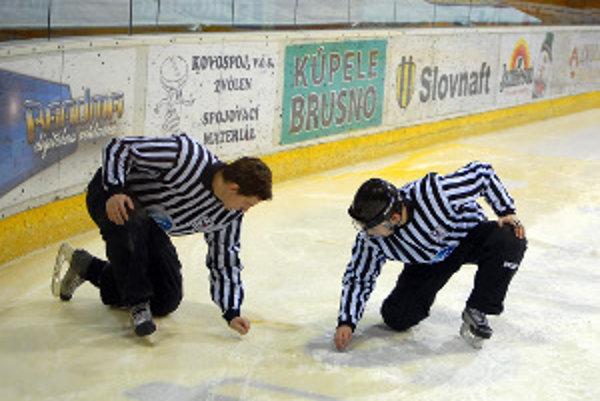 Čiaroví rozhodcovia upravujú povrch ľadu, ktorý poškodila rolba.