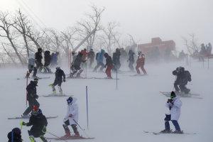 Pretekárky si obhliadajú trať slalomu, opäť však silno fúka.