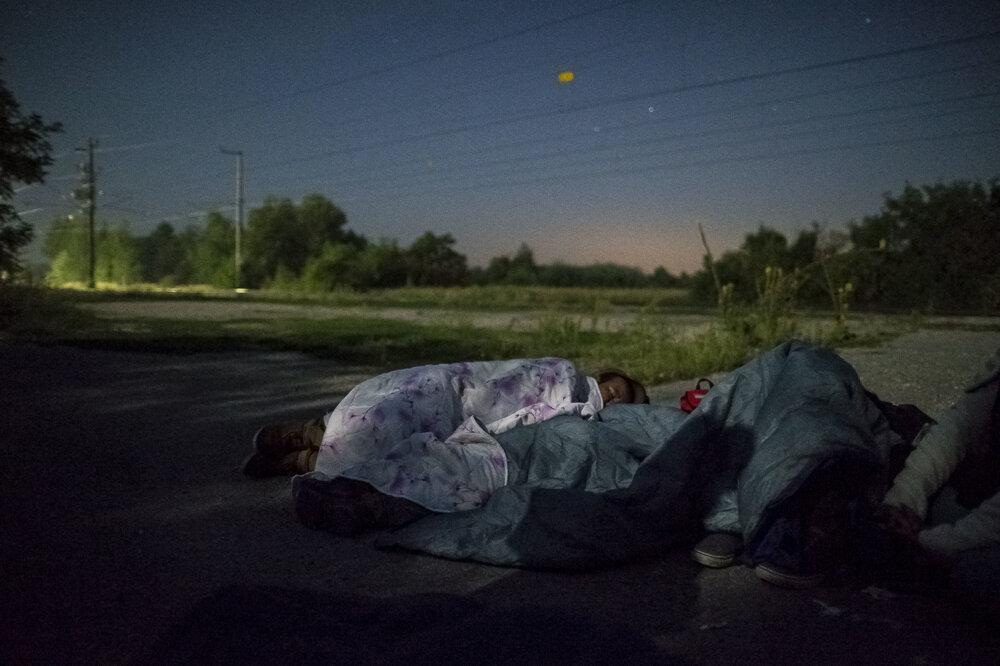 Rodina Ujgurov spí na betóne blízko stanice vNickelsdorfe. Krátko pred tým prekročili hranice zMaďarska. Vtedy bola hranica ešte zatvorená, preto sa skrývali vtme pod stromami. Prezradilo ich len slabučké svetlo ztelefónu.