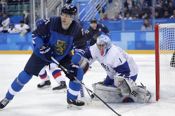 Fínsky hokejista Joonas Kemppainen sa dostáva k puku pred juhokórejským brankárom Mattom Daltonom.