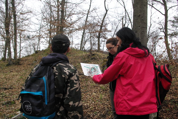 Archeologička si pozerá vizualizáciu pôvodnej podoby hrádku.