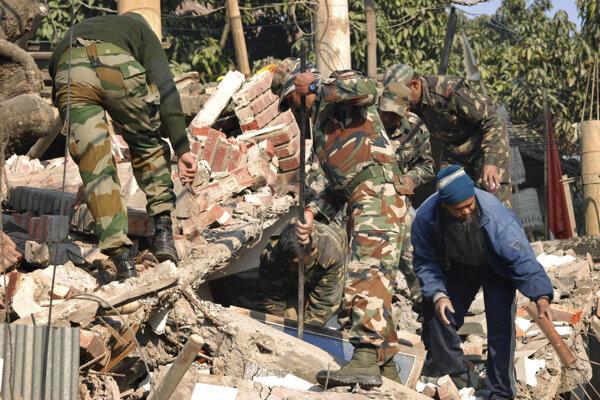 Indickí vojaci a miestni obyvatelia prehľadávajú budovu, ktorá sa zrútila počas zemetrasenia v indickom Imphále.