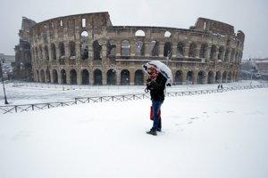 Muž  pred rímskym Koloseom počas sneženia.