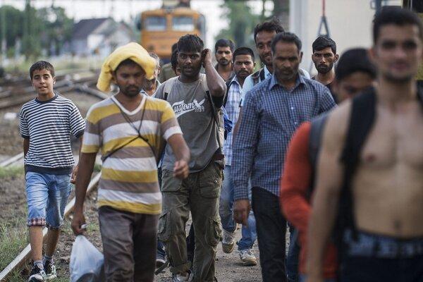 Migranti kráčajú cez koľajnice železničnej stanice  v maďarskom meste Kiskunhalas