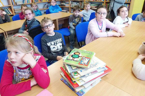 Deti vknižnici pozorne počúvajú príbeh čítaný zknihy.