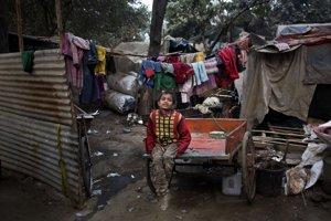 Indický chlapec sedí na káre v slumoch v Nai Dílí.