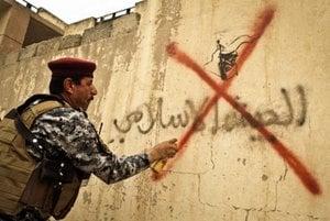 Iracký vojak preškrtol nápis za islamistickú armádu.