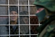 Ukrajinský námorník sleduje cez okno veliteľstva námorníctva vSevastopoli ruského vojaka. (AP Photo/Andrew Lubimov)