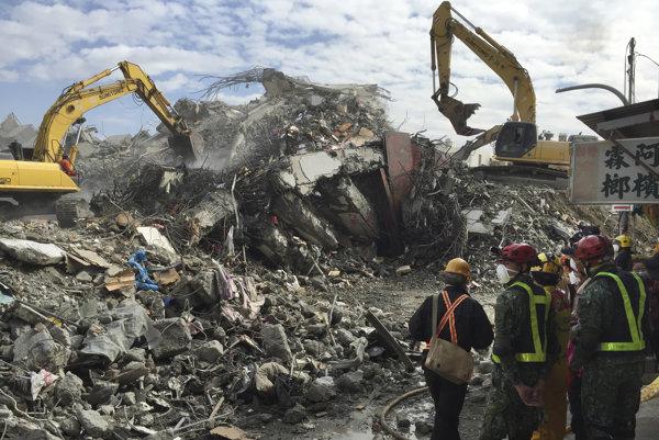 Stavební robotníci s ťažkými mechanizmami postupne likvidujú trosky zrútenej budovy v Tchaj-nane.