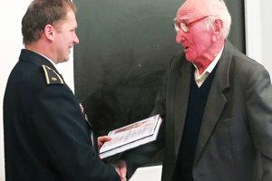 Ondrej Krúpa (vpravo) si preberá vyznamenanie od hasičov za 70-ročnú službu.