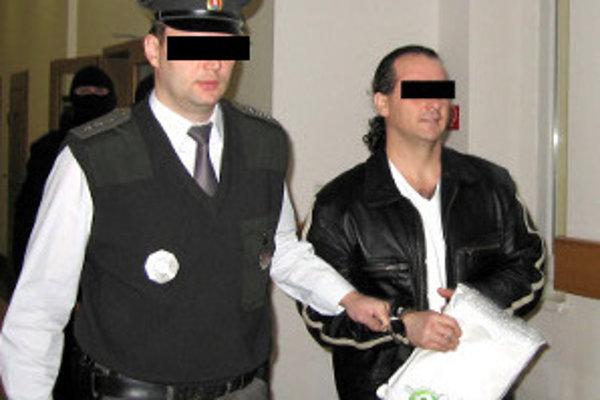 Policajt vedie údajného mafiána z pojednávania na Okresnom súde Žilina.