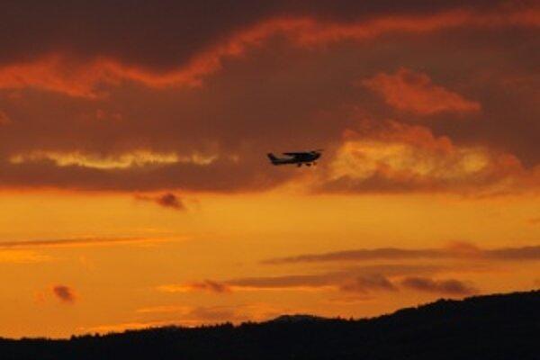 Odlet lietadla zo žilinského letiska v Dolnom Hričove pri západe slnka.