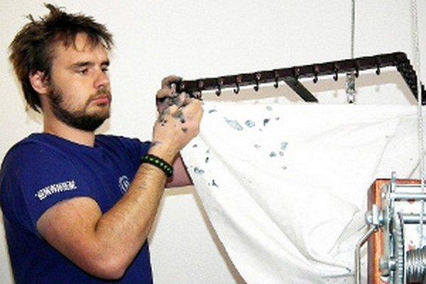 Matej Rabada napína na rám potlačenú bavlnu.