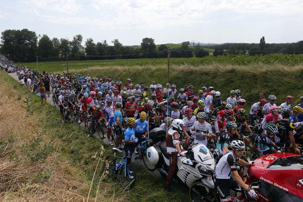 Cyklisti čakajú na ceste po tom, čo 16. etapu Tour de France 2018 prerušil štrajk farmárov.