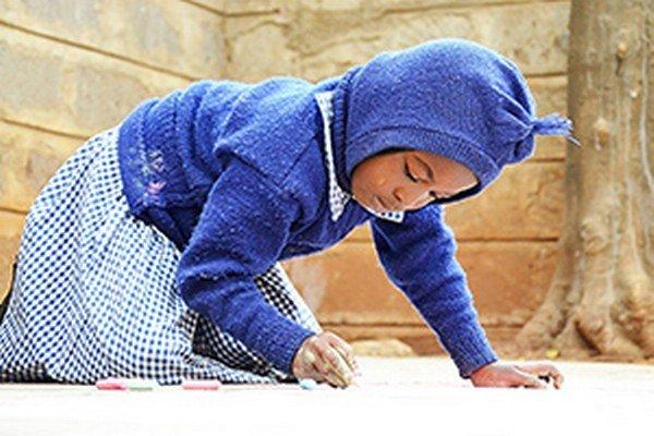 Malá Teresia kreslí kriedami na chodník pred školou.