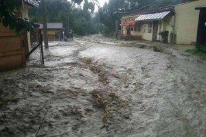 Po silnej búrke rozvodnený potok zalial cesty a rodinné domy.