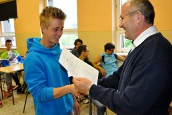 Tomáš Kurňavka si z rúk profesora preberá posledné vysvedčenie na pôde školy v Istebnom.