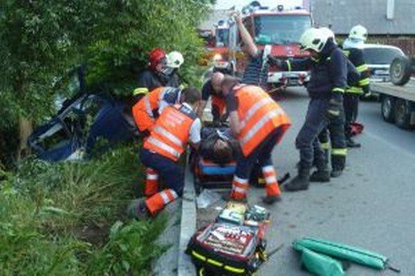Zdravotníci poskytujú prvú pomoc ťažko zranenému vodičovi.