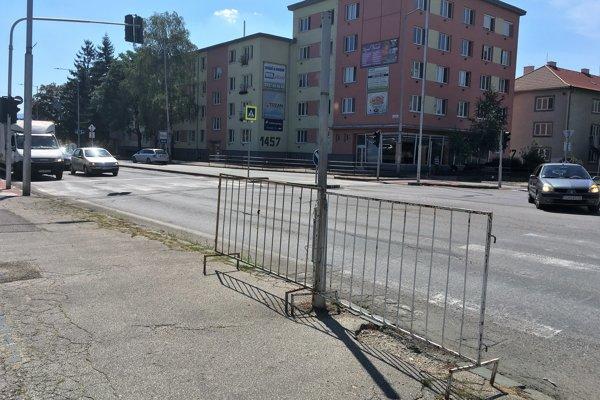 Dočasné zábradlie priviazané o zrušený stĺp semaforu.