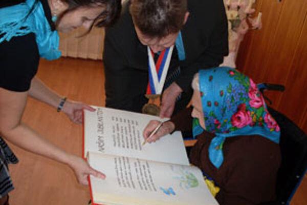 Všetci jubilujúci Lesňania sa podpísali do obecnej kroniky. Medzi nimi aj 93-ročná Rozália Pojezdalová.